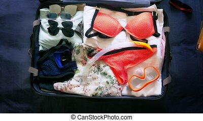close-up. girl collects a suitcase for rest in warm countries with scuba diving gear in the sea