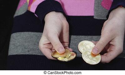close-up girl counts  golden bitcoin