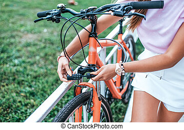 Close-up girl hand lock with digital cipher. Woman summer stands bicycle locking bicycle with cable. Picks password lock, theft bicycle parking lot. Bicycle rentals Cycling weekend. Active lifestyle.
