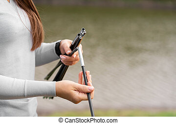 Close-up girl holding rods for camping tent. Camping with a tent. Lake on the background