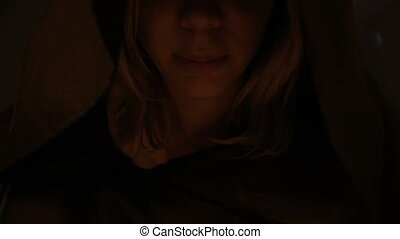 Close-up girl magician in the hood in a dark room by...