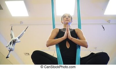 Close-up. Girl sitting in the lotus position in a hammock to fly yoga