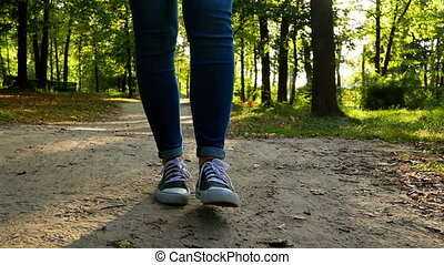 Close-up girl walking forest