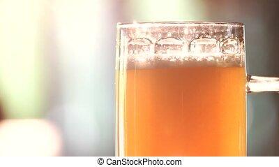 Close up glass of light ale rotating.