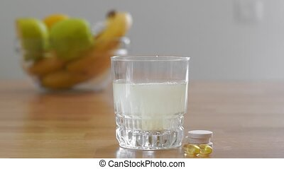 Close up glass with water and sparkling pill. Magnesium anti-stress, painkiller or orange drink. High quality 4k footage