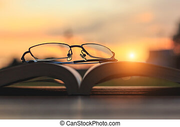 Close up glasses and book on table in sunset time