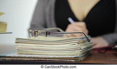 close-up glasses on a exercise books, teacher works without...