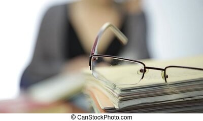glasses on a pile of exercise books, woman works without...
