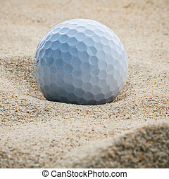 Close up golf ball in sand bunker shallow depth of field. A golf ball plugged deep in sand trap.