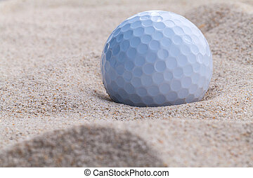 Close up golf ball in sand bunker shallow depth of field.