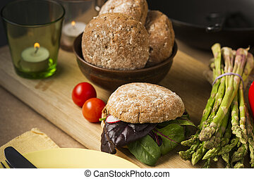 Close up Gourmet Healthy Food with Bread and Veggies on Wooden Board, Emphasizing Leafy Vegetables, Asparagus and Tomatoes