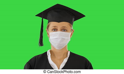 Graduate student lady in a medical mask looking to camera on a Green Screen, Chroma Key.