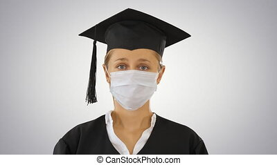 Graduate student lady in a medical mask looking to camera on gradient background.