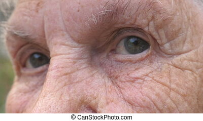 Close up gray eyes of elderly woman with wrinkles around...