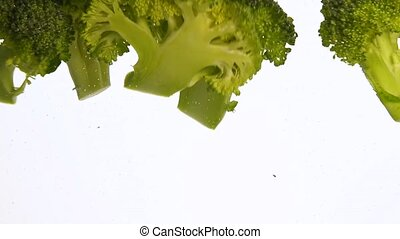 Close up green broccoli thrown floating in water - Close up...