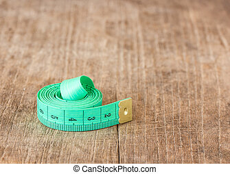 Close up green measuring tape on wooden table