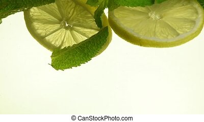 Close up green mint leaves and lemon in mojito - Close up...