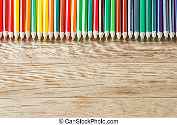 Close up green pencils on wooden background, direct position...
