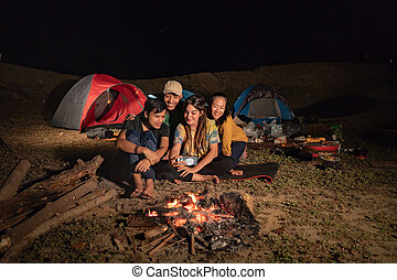 close up group of friends camping, selfie around camp fire