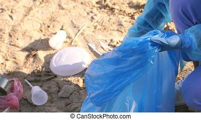 Close-up group of young people in shirts and gloves collect garbage on the beach
