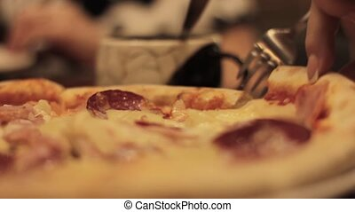 close-up hand cuts and eats a slice of pizza in a cafe. Man...