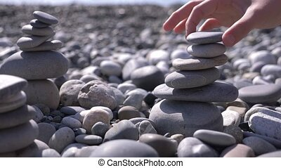 close-up, hand folds a pyramid of stones on the seashore. 4k, slow motion