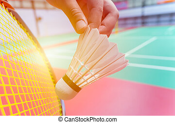 close up hand hold serve badminton shuttlecock with blur ...