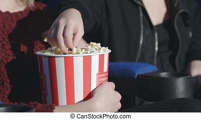 Close up hand holding a bucket of popcorn