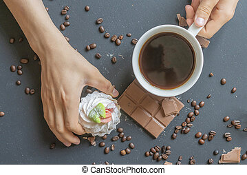 close up hand holding a sweet cake and a cup of coffee on the dark table in the morning f