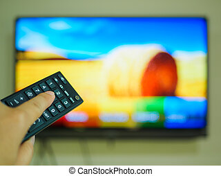 Close up Hand holding TV remote control with a television in the background.