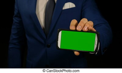 Close up hand of a businessman holding smart phone with green screen