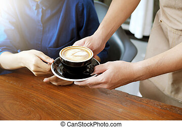 Close-up hand of a waitress serving a cup of coffee to...