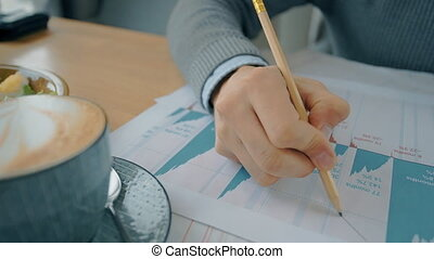 Close up hand of businessman drawing market tendencies on graphs during lunch in cafe.