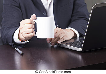 Businessman holding cup of coffee