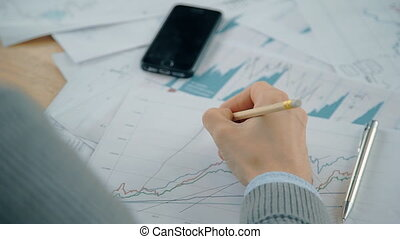Close up hand of businessman working on graph with market...