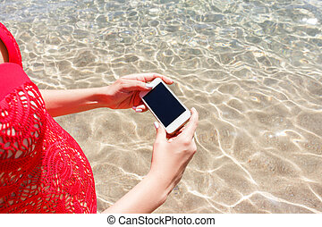 Close up hand of woman holding smartphone and take photo standing in the sea