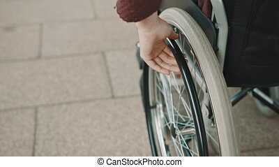 close up, hand of young woman steering the wheel of the wheelchair.