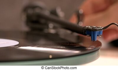 Close up hand turning on vintage record player. Needle playing retro music. Turntable music device.