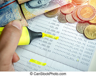 Close-up hand with yellow marker pen highlighting on the deposit money, account statement in saving account passbook.