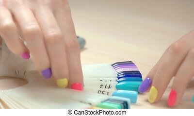 Close up hands and nail polish samples. Girl hand with...