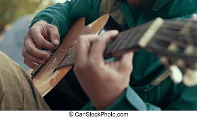 Close up hands man playing music on strings guitar