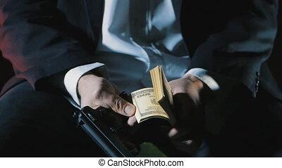 close-up hands of a dangerous man with a gun counts the money. Dirty Money Mafia.