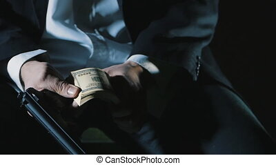 close-up hands of a dangerous man with a gun counts the money. Dirty Money Mafia.