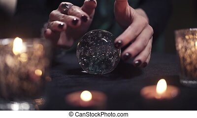 Close-up hands of a female magician being drifted over a glass ball during a spiritualism session. Concept of magic and the disclosure of fate