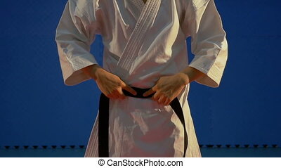Close up hands of a man putting on his black belt on his white karate kimono in slow motion