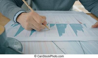 Close up hands of businesman workig on market situation graphs in cafe.