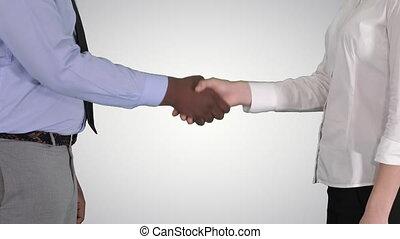 Hands of businessman and businesswoman handshaking on gradient background.