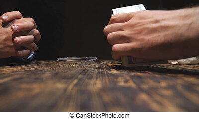 Close up hands of businessman putting a bundle of foreign currency on the table. Male arms of drug dealer taking money, giving cocaine for customer and shaking hands for each other. Side view.