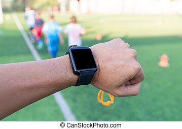 Close-up hands of Coach using his smart watch is coaching Children Training In Soccer Team