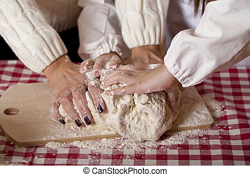 Close up hands of family are baking cakes in home kitchen